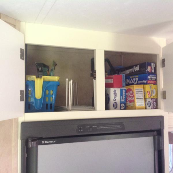 Storage above fridge.  Paper products stay in cabinet year round