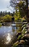 A young family standing on a walk-bridge over the Mississippi River; at it's beginning; Itasca, MN