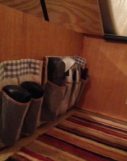 I cut a shoe pocket organizer into strips, sewed fabric along the top and attached grommets, then hung them on the side of the bed platform under the mattress.  If I do it again, I'll mount them higher.  I bumped my toes into the shoes a lot and it was hard to sweep under them.