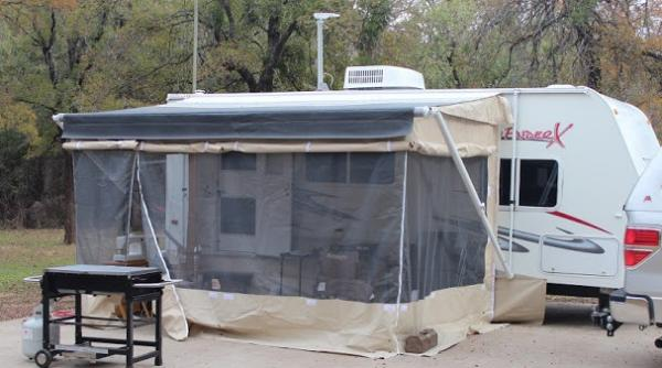 """It came with a screened room that had never been used. It had to be fitted to the trailer and awning, but once that was done, set up was pretty easy. This was Hubby's favorite part of the trailer. Officially, it was called a Dometic Patty O'Room. An added benefit to it was that it kept the awning stable in a breeze. We took it down for big storms, but a breeze that would send other awnings over the top of the trailer was no problem here. We seldom used it with the vinyl """"walls"""" down.  You can see them rolled up around it. At this particular campground, we were on a huge concrete pad so couldn't drive the stakes into the ground. hubby had to improvise for a day."""