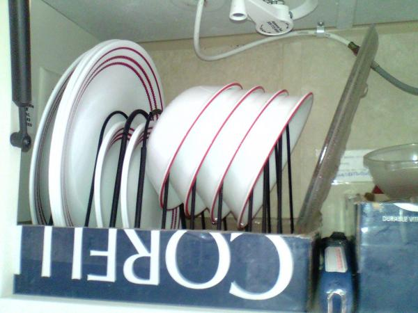 I use a wire file folder rack to store my dishes in the cabinet above the sink.  It sits in a cardboard box lid to keep it in place.