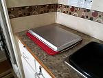 I cover the stove with a dish drying pad and a metal tray that gives me work kitchen work surface.  The pad keeps it in place while traveling.