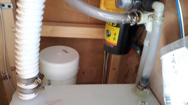 """I can't believe the original sewer hose storage didnt even fit a 10 foot hose with a clamp on connector on one end. I had to cut down to about 7.5 feet, which really sucked. Here is the extension I added, now 38"""" total, compared to the original 20"""" long tube. You can see it poking out behind the fresh water tank.  I can fit a full 20 foot hose now. Just a piece of 4"""" pvc sewer line amd a cap and some contact cement."""